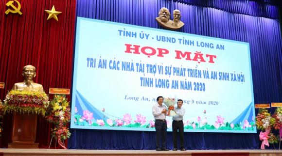 Ông Phạm Văn Rạnh, Bí thư Tỉnh ủy Long An (trái) tặng hoa tri ân cho Nguyên Chủ tịch nước Trương Tấn Sang /// ẢNH: B.B