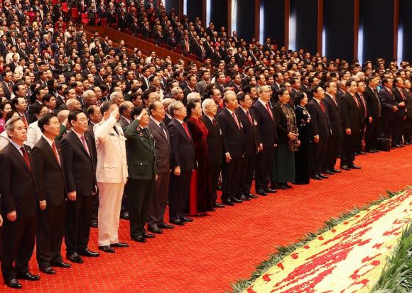 Các đại biểu thực hiện nghi thức chào cờ tại phiên khai mạc Đại hội XIII, sáng 26/1. Ảnh: TTXVN