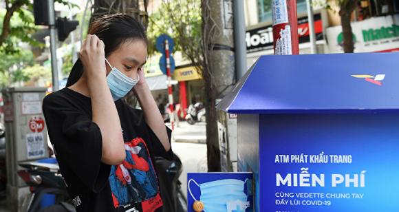 Cô gái đeo khẩu trang y tế tại máy bán khẩu trang miễn phí ở Hà Nội, Việt Nam