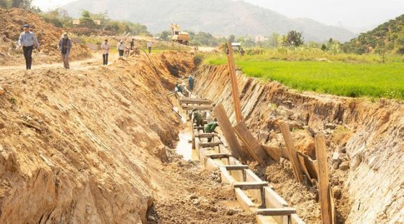 Đoạn kênh đang được thi công nằm sâu dưới lòng đất, thấp hơn bề mặt ruộng lúa gần 3 m /// ẢNH: THANH QUÂN